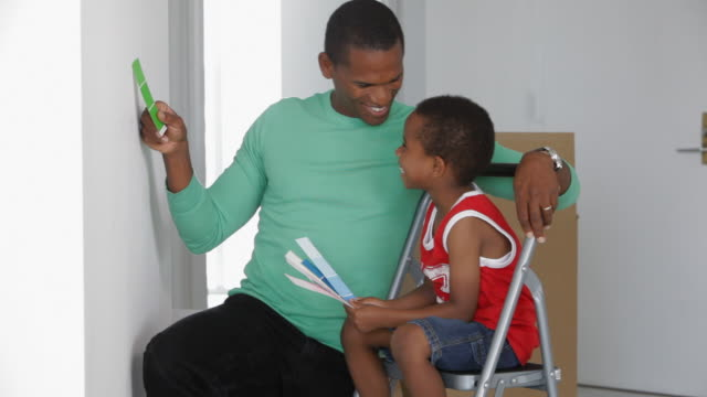 African American father with son checking paint colors