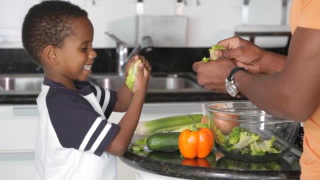 african american father with son preparing salad - オレンジピーマン点の映像素材/bロール