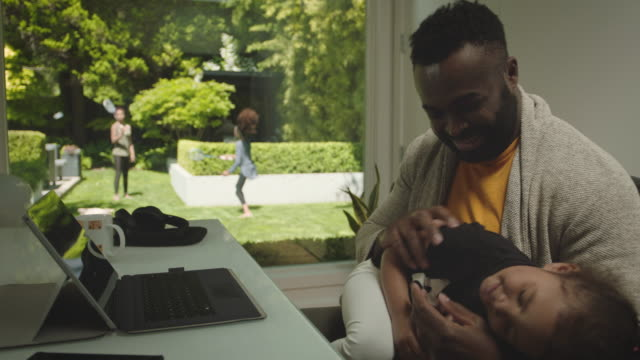 African American Father working from backyard home office with daughter and kids playing outside