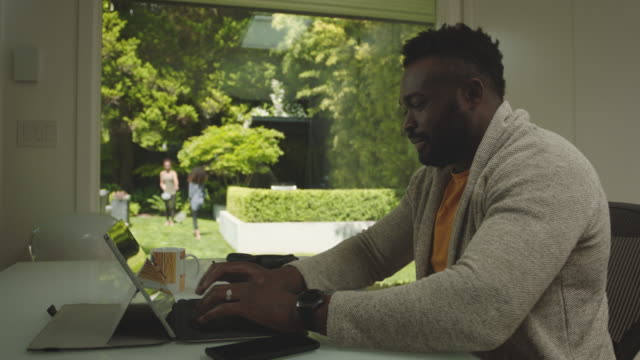 African American Father working from backyard home office with kids playing outside