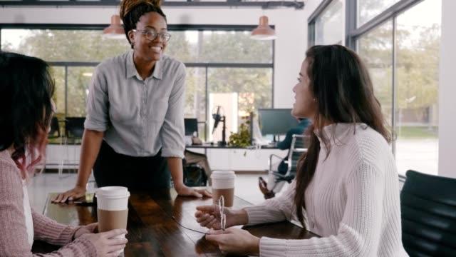 afroamerikansk kvinnlig affärsman ger presentation till kvinnliga kollegor - engångsmugg bildbanksvideor och videomaterial från bakom kulisserna