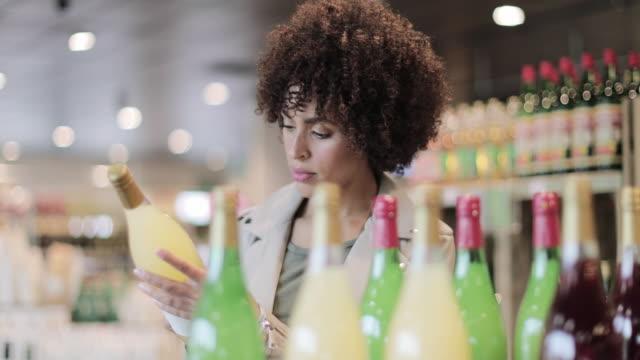 vídeos y material grabado en eventos de stock de african american female shopping in a grocery store - super slow motion