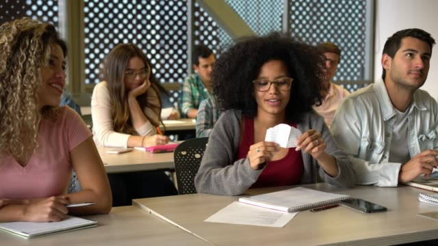 african american female student receiving a note from a friend during class while other students are paying attention - blocco per appunti video stock e b–roll