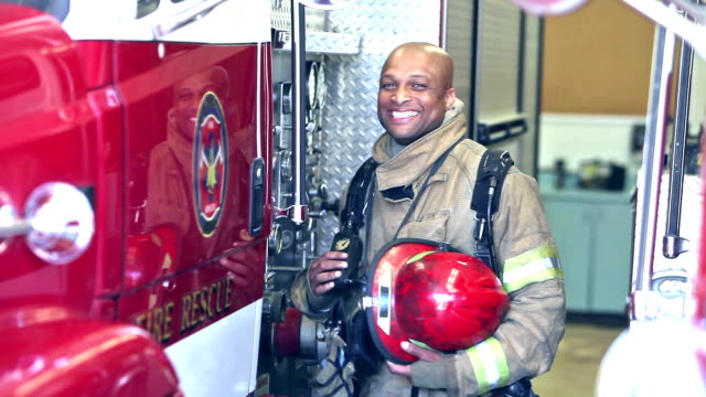 african american fireman standing by truck at station - firefighter stock videos and b-roll footage