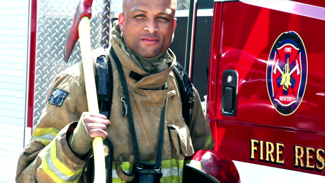 african american fireman standing by truck with axe - firefighter stock videos & royalty-free footage