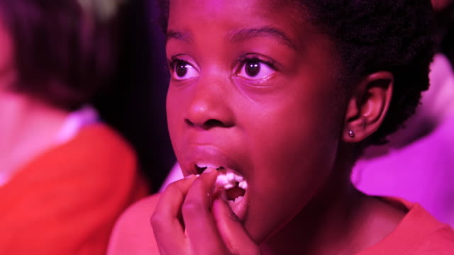african american girl glued to screen in movie theatre, close up - cinema stock videos & royalty-free footage