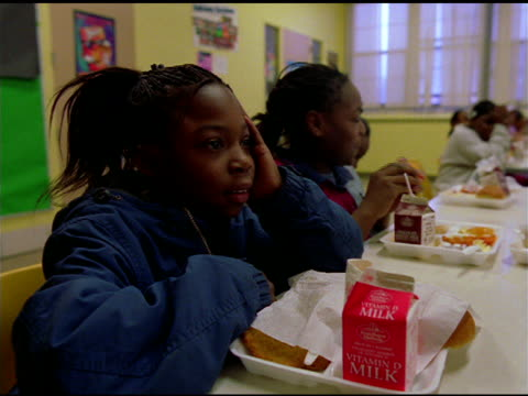 African American girl sitting in school canteen with tray of food and carton of milk laughs, Chicago