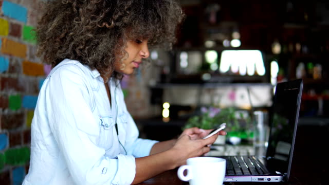 african american girl using smart phone in cafe - curly stock videos & royalty-free footage