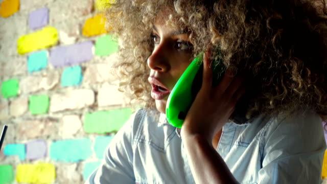 afroamerikanische mädchen mit smartphone im café - weibliche angestellte stock-videos und b-roll-filmmaterial