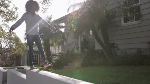 african american girl walking carefully along a wall balancing - balance stock videos & royalty-free footage
