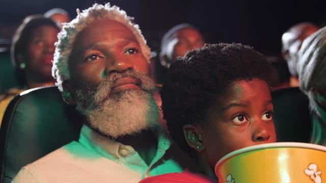 vídeos y material grabado en eventos de stock de african american grandfather and granddaughter share seat in movie theatre, close up - industria cinematográfica