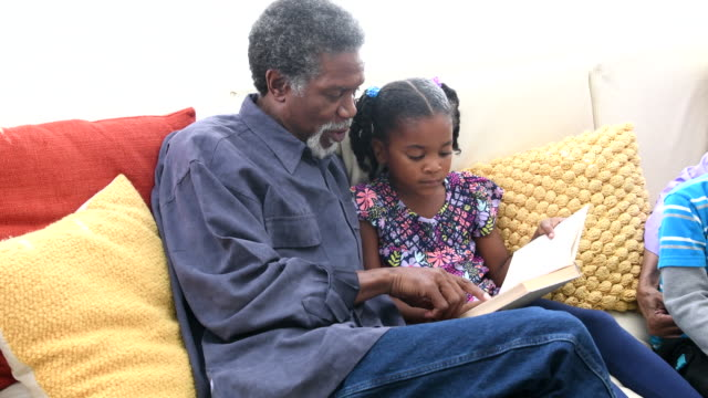 african american grandfather reading book to young girl on sofa - granddaughter stock videos & royalty-free footage
