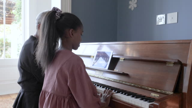 african american grandmother and grand daughter play piano, close up - musikinstrument stock-videos und b-roll-filmmaterial