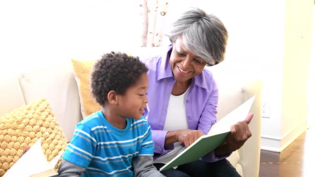 vídeos de stock, filmes e b-roll de avó americana africano mostrando neto um livro, sorrindo - avó