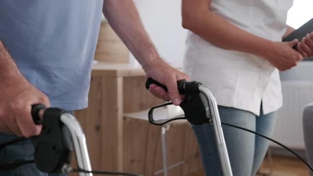 african american healthcare worker helping a senior man with a mobility walker - mobility walker stock videos and b-roll footage