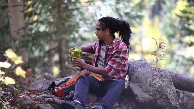 vidéos et rushes de african american hiker in the aspens - bouteille d'eau minérale