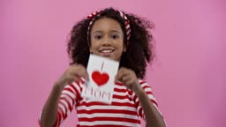 african american kid with greeting card on mothers day isolated on pink