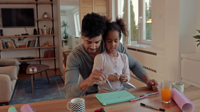 african american little girl writing note on wrapped present while father is assisting her. - wrapping paper stock videos & royalty-free footage