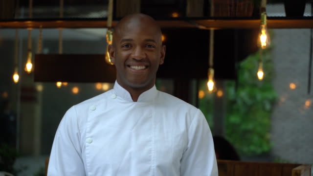african american male chef at a restaurant facing camera smiling - gourmet stock videos & royalty-free footage