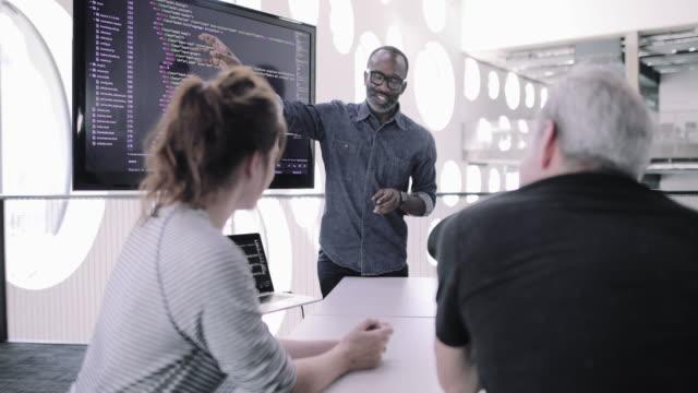 african american male game designer leading a meeting - フリーアドレス点の映像素材/bロール