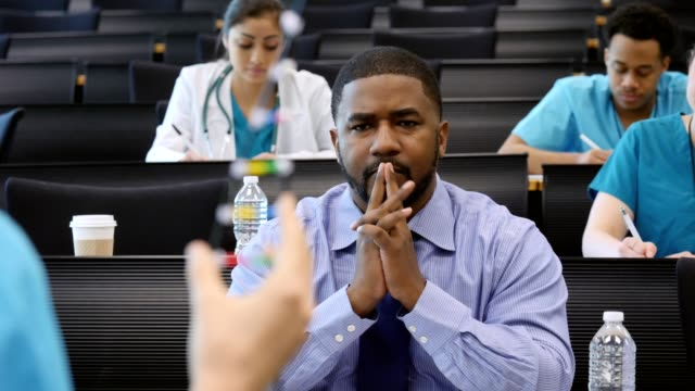 african american male healthcare professional asks medical conference speaker a question - lecture hall stock videos & royalty-free footage