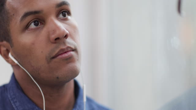 vídeos de stock, filmes e b-roll de african american male listening to audio with headphones - fones de ouvido intracanal
