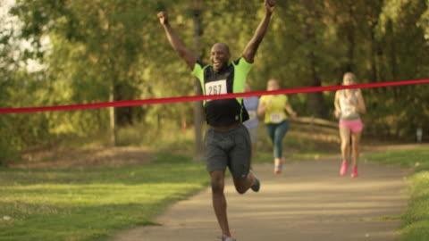 vídeos y material grabado en eventos de stock de africano american hombre corriendo un través de una cinta y acabado línea durante la raza - línea de meta