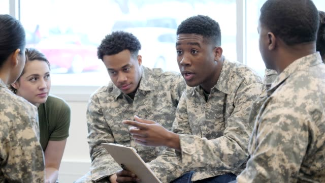 African American male soldier talks with group of cadets