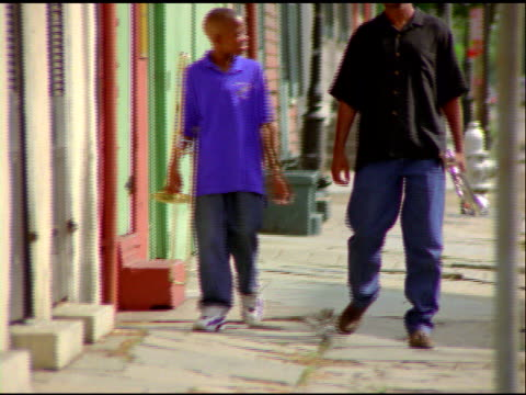 african american man and boy walk along street towards camera carrying wind instruments with arms around each other - menschliche gliedmaßen stock-videos und b-roll-filmmaterial