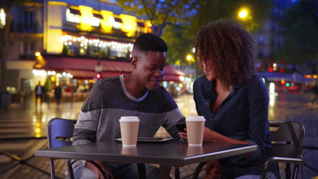 african american man and woman drink coffee and use smartphone on paris street - coffee drink stock videos & royalty-free footage