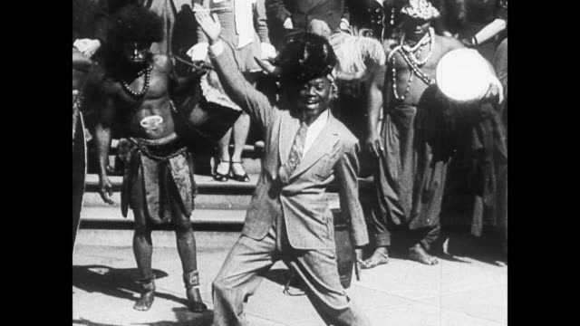 / african american man dancing in street while men stand behind him in traditional african costume swing dancing on january 01 1935 - 1935 stock videos & royalty-free footage