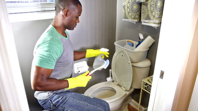 african american man doing chores, cleaning toilet - forehead stock videos and b-roll footage