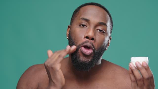 stockvideo's en b-roll-footage met afrikaanse amerikaanse mens houdt roompot en is op gezicht van toepassing - poreus