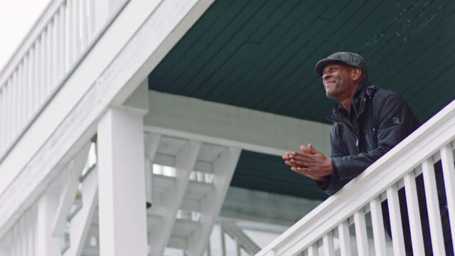 MS SLO MO. African American man in jacket leans over railing of outdoor porch balcony, smiles and rubs hands together as he enjoys the view.