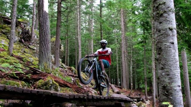 森の中でマウンテンバイクに乗っているアフリカ系アメリカ人の男 - クロスカントリーサイクリング点の映像素材/bロール
