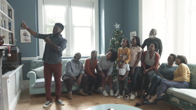 african american man takes selfie of family on christmas, medium shot - large family stock videos & royalty-free footage