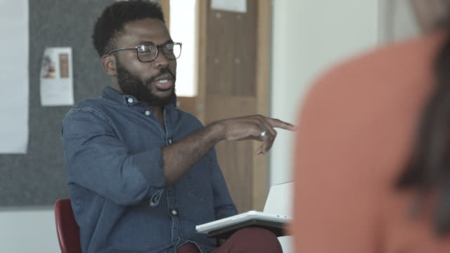 vidéos et rushes de african american man talks to college students, close up - professor