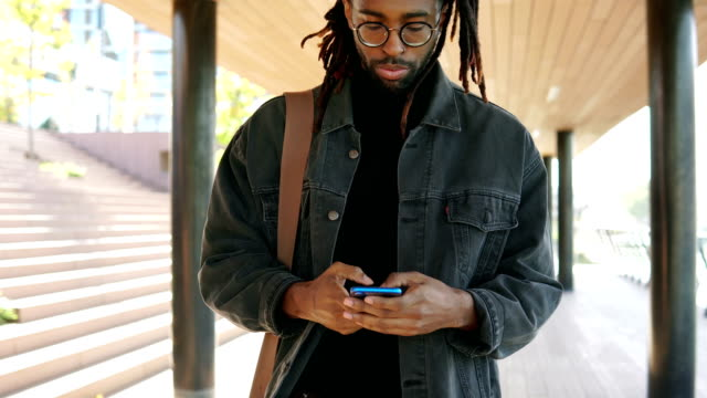 african american man texting on a phone - locs hairstyle stock videos & royalty-free footage