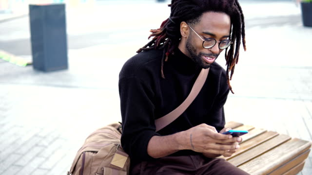 african american man using phone outdoor - locs hairstyle stock videos & royalty-free footage