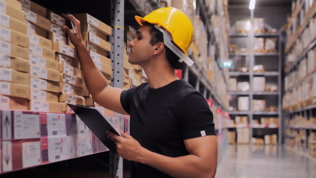 african american man working in a warehouse and checking quality of manufactured products before the distribution.warehouse and people concept. - african american ethnicity stock videos & royalty-free footage