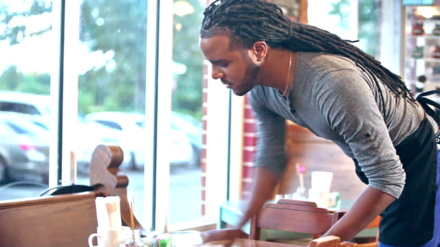 African American man working in coffee shop wiping table