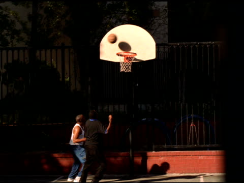 vídeos de stock e filmes b-roll de african american men playing one on one basket ball, one jumps up and scores basket, san francisco - san francisco