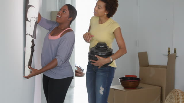 African American mother and daughter hanging african sculpture
