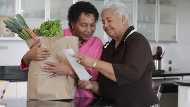 vidéos et rushes de african american mother and daughter looking at groceries in kitchen - sachet en papier
