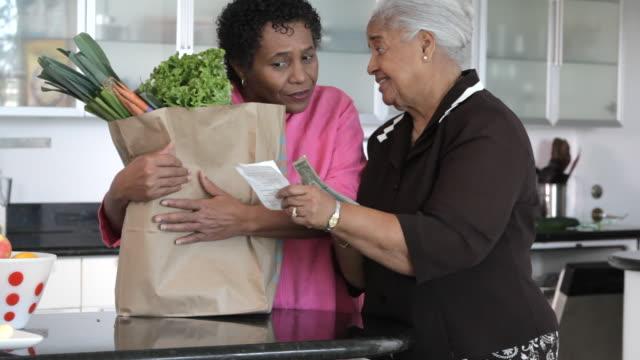 african american mother and daughter looking at groceries in kitchen - papperskasse bildbanksvideor och videomaterial från bakom kulisserna