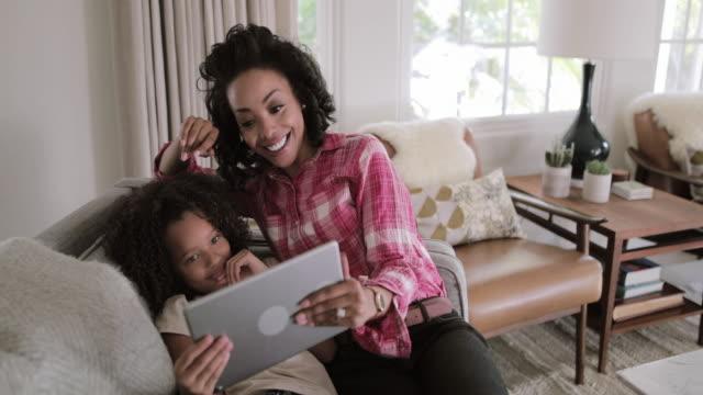 vídeos y material grabado en eventos de stock de african american mother and daughter using digital tablet for a videocall - voz sobre ip