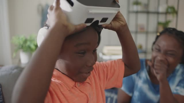 african american mother smiles and laughs as young son reacts to virtual reality headset. - erweiterte realität stock-videos und b-roll-filmmaterial