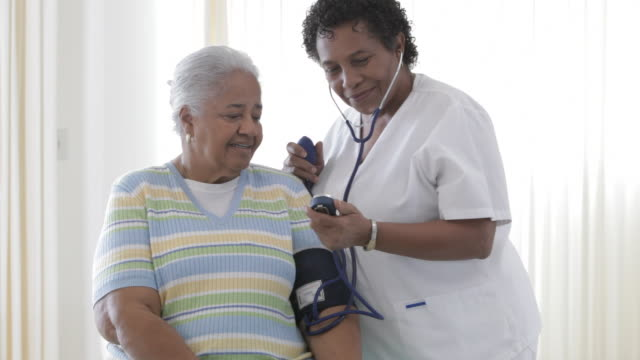African American nurse taking senior patient's blood pressure