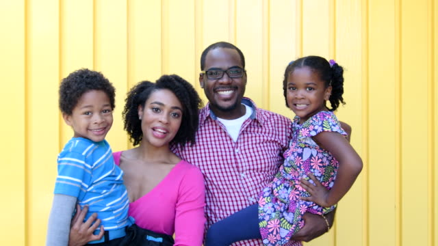 African American parents with two children smiling