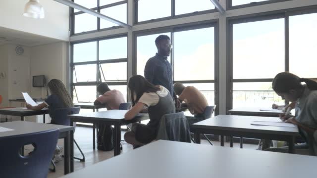 stockvideo's en b-roll-footage met african american professor watches students take exam, slow motion - 20 29 jaar
